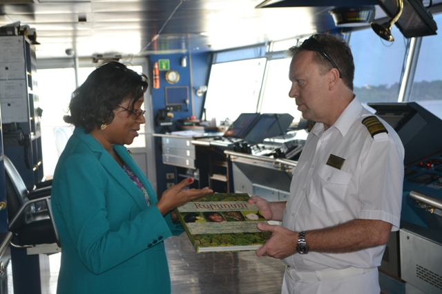 Minister of Tourism Cathy Hughes presents a book on the Rupununi to Captain of the Minerva, Neil Broomhall
